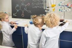 Enfants portant des manteaux de laboratoire et étudiant dans le laboratoire de science image libre de droits