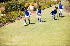 Enfants portant l'uniforme du football jouant un match Photo libre de droits
