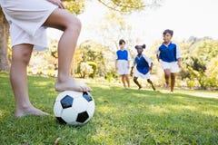 Enfants portant l'uniforme du football jouant un match Photo stock