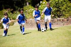 Enfants portant l'uniforme du football jouant un match Photographie stock libre de droits