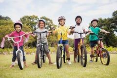 Enfants posant avec des vélos Images libres de droits