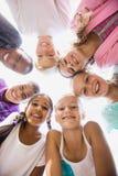 Enfants posant ensemble pendant un jour ensoleillé à l'appareil-photo Images stock