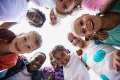 Enfants posant ensemble pendant un jour ensoleillé à l'appareil-photo Photo stock