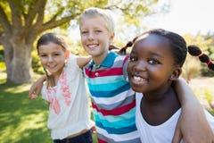Enfants posant ensemble pendant un jour ensoleillé à l'appareil-photo Image stock