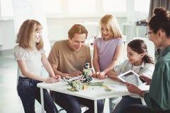 Enfants positifs et professeurs jouant avec des jouets photographie stock