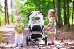 Enfants poussant la poussette avec le bébé nouveau-né Image stock