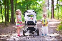 Enfants poussant la poussette avec le bébé nouveau-né Photographie stock