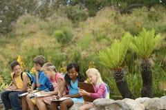 Enfants préparant des notes pendant l'excursion sur le terrain Photo stock