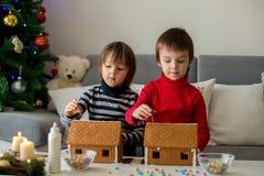 Enfants préscolaires adorables, frères de garçon, décorant le gingerbrea Photos stock