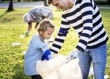 Enfants prenant des déchets en parc avec des parents images libres de droits