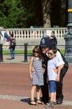 Enfants prenant des photos avec le policier Images stock