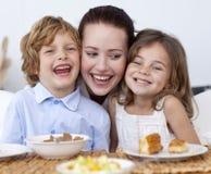 Enfants prenant le petit déjeuner avec leur mère Image libre de droits