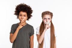Enfants résolus sérieux posant avec les bouches attachées du ruban adhésif photos stock