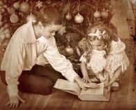Enfants recevant des cadeaux sous l'arbre de Noël Image stock
