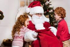 Enfants recherchant des cadeaux dans le sac de Santa Photos stock