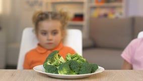 Enfants regardant avec dégoût le brocoli, refusant de manger les légumes sains banque de vidéos