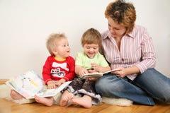 Enfants regardant des livres avec la mère Photos libres de droits