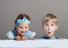 Enfants regardant l'appareil-photo par derrière la table Photographie stock libre de droits