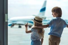 Enfants regardant la fenêtre dans l'aéroport images libres de droits