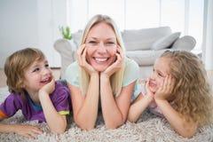 Enfants regardant la mère se trouvant sur la couverture Images stock