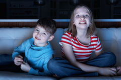 Enfants regardant la TV se reposer ensemble sur le sofa Image stock