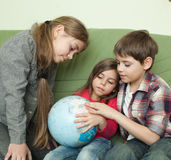 Enfants regardant le globe Images stock