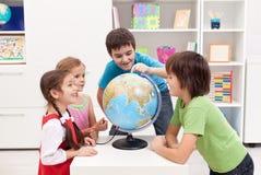 Enfants regardant le globe de la terre Images libres de droits