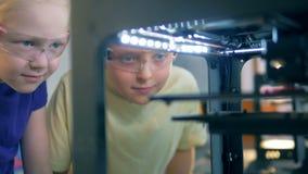 Enfants regardant un fonctionnement moderne d'imprimante de l'école 3D Concept moderne d'éducation banque de vidéos