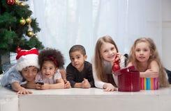Enfants retenant des cadeaux de Noël Photographie stock libre de droits