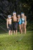 Enfants riant et criant par l'arroseuse de pelouse Images libres de droits