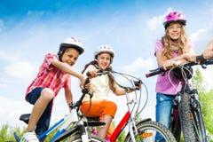 Enfants riants dans des guidons de vélo de prise de casques Photos libres de droits