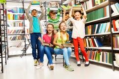 Enfants riants heureux enthousiastes dans la bibliothèque Images stock