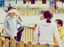 Enfants riants jouant au bluff d'homme aveugle Image stock