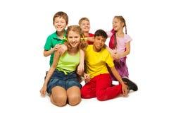 Enfants riants s'asseyant sur le plancher ensemble Image stock