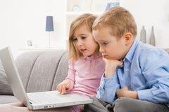 Enfants sérieux avec l'ordinateur portatif Photos libres de droits