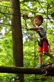 Enfants s'élevant en parc d'aventure Le garçon a plaisir à s'élever dans l'aventure de cours de cordes images stock