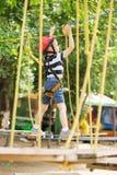 Enfants s'élevant en parc d'aventure Le garçon a plaisir à s'élever dans la corde photo libre de droits