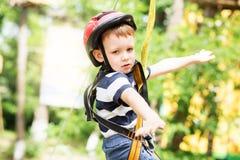 Enfants s'élevant en parc d'aventure Le garçon a plaisir à s'élever dans la corde image stock