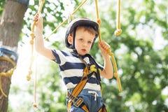 Enfants s'élevant en parc d'aventure Le garçon a plaisir à s'élever dans la corde photos stock