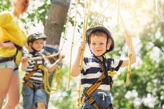 Enfants s'élevant en parc d'aventure Le garçon a plaisir à s'élever dans la corde photo stock