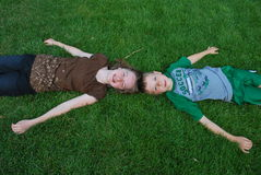 Enfants s'étendant sur l'herbe Photo libre de droits