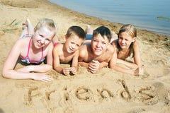 Enfants s'étendant sur la plage Image stock