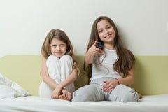 Enfants s'asseyant à la maison dans le lit et la TV de observation Dans les mains jugeant la TV à distance Photographie stock libre de droits