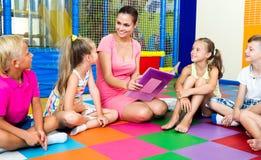 Enfants s'asseyant autour du livre de lecture de professeur Images stock