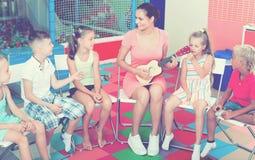 Enfants s'asseyant autour du professeur avec la petite guitare Images libres de droits