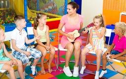 Enfants s'asseyant autour du professeur avec la petite guitare Photographie stock libre de droits