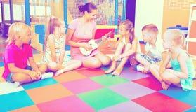 Enfants s'asseyant autour du professeur avec la petite guitare Photos stock