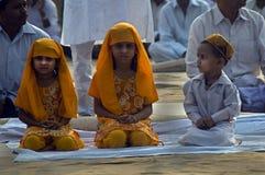 Enfants s'asseyant aux prières d'identification Images libres de droits