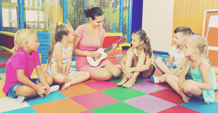 Enfants s'asseyant avec le professeur et écoutant la musique dans la classe Photo libre de droits