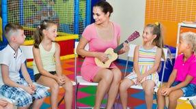 Enfants s'asseyant avec le professeur et écoutant la musique dans la classe Images libres de droits